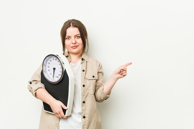 Jovem mulher curvilínea segurando uma balança sorrindo e apontando para o lado, mostrando algo no espaço em branco.