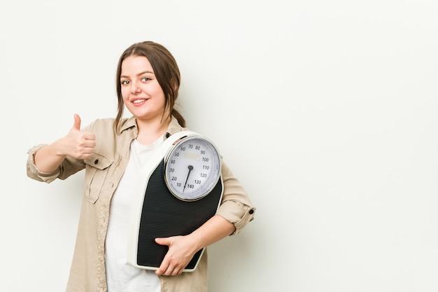 Jovem mulher curvilínea segurando uma balança sorrindo e levantando o polegar