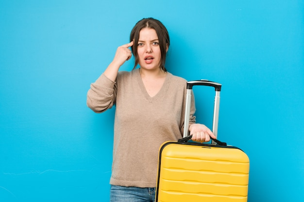 Jovem mulher curvilínea segurando uma mala mostrando um gesto de decepção com o dedo indicador.