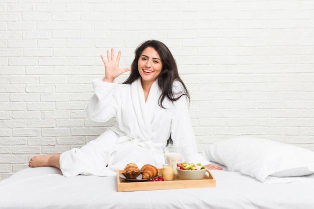 Jovem mulher curvilínea tomando café da manhã na cama sorrindo alegre mostrando o número cinco com os dedos.