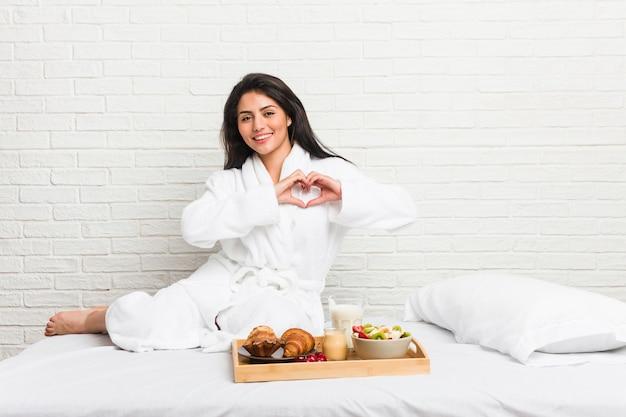 Jovem mulher curvilínea tomando café da manhã na cama sorrindo e mostrando uma forma de coração com as mãos.