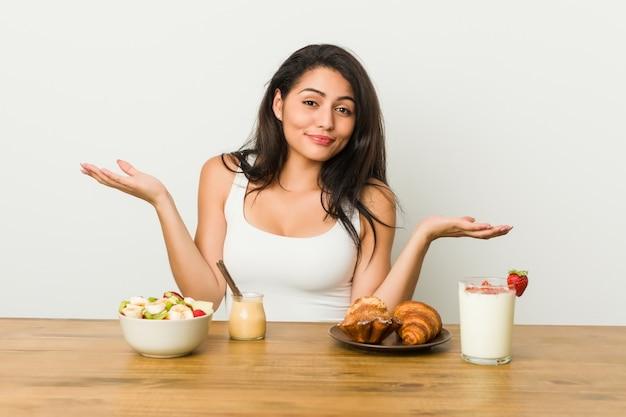 Jovem mulher curvilínea tomando um café da manhã duvidando e encolher os ombros os ombros em gesto de questionamento