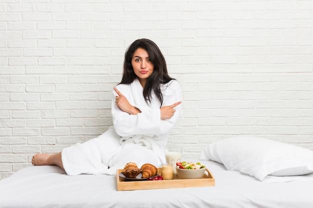 Jovem mulher curvilínea tomando um café da manhã na cama aponta lateralmente, está tentando escolher entre duas opções.
