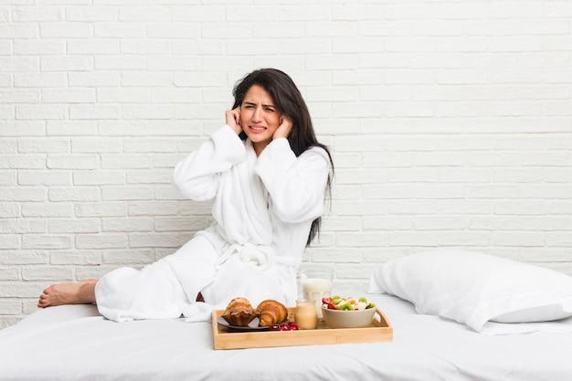 Jovem mulher curvilínea tomando um café da manhã na cama cobrindo os ouvidos com as mãos.