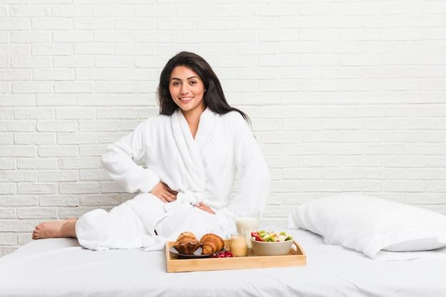 Jovem mulher curvilínea tomando um café da manhã na cama confiante, mantendo as mãos nos quadris.