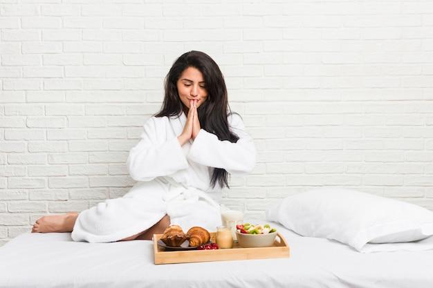 Jovem mulher curvilínea tomando um café da manhã na cama de mãos dadas em rezar perto da boca, sente-se confiante.