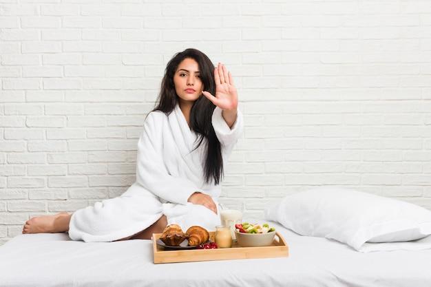Jovem mulher curvilínea tomando um café da manhã na cama em pé com a mão estendida, mostrando o sinal de stop