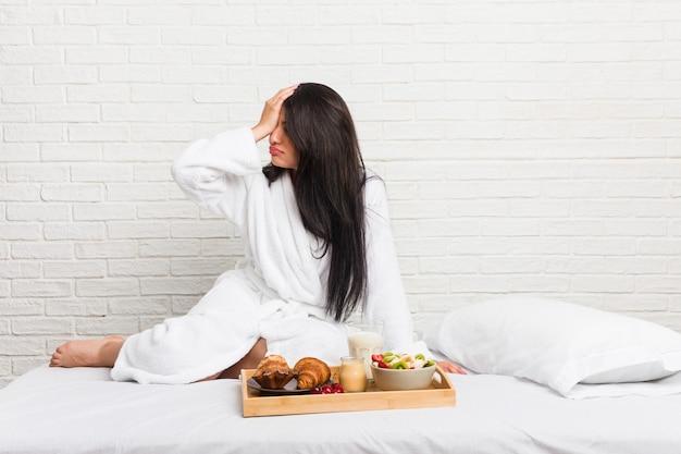 Jovem mulher curvilínea tomando um café da manhã na cama esquecendo algo, batendo na testa com a palma da mão e fechando os olhos.