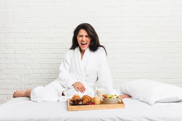 Jovem mulher curvilínea tomando um café da manhã na cama gritando muito irritado e agressivo