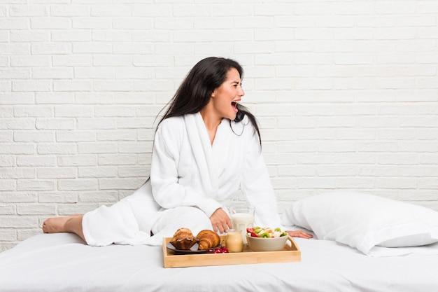 Jovem mulher curvilínea tomando um café da manhã na cama gritando para um espaço de cópia