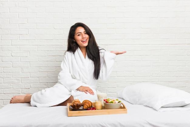 Jovem mulher curvilínea tomando um café da manhã na cama