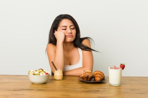 Jovem mulher curvilínea tomando um café da manhã que se sente triste e pensativo, olhando para o espaço da cópia.