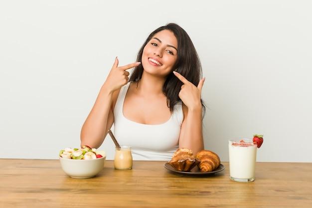 Jovem mulher curvilínea tomando um café da manhã sorri, apontando os dedos na boca.