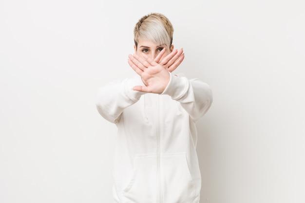 Jovem mulher curvilínea vestindo um capuz branco, fazendo um gesto de negação