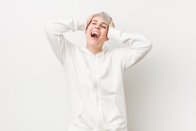 Jovem mulher curvilínea vestindo um capuz branco ri alegremente, mantendo as mãos na cabeça. felicidade.