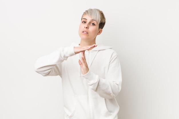 Jovem mulher curvilínea vestindo um moletom branco, mostrando um gesto de tempo limite.