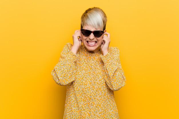 Jovem mulher curvilínea vestindo uma roupa de verão floral coning orelhas com as mãos.