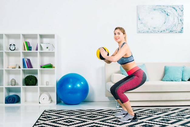 Jovem mulher da aptidão que exercita com a bola médica na ginástica em casa