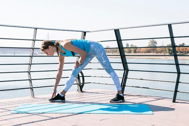 Jovem mulher da aptidão que faz o exercício no ar livre