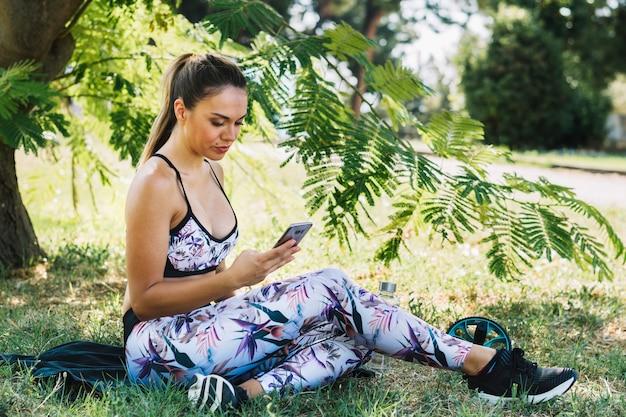 Jovem mulher da aptidão que senta-se no jardim usando o smartphone