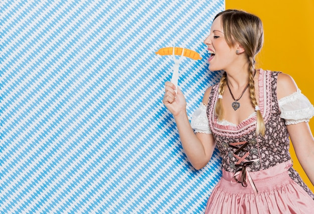 Jovem mulher da baviera, segurando o garfo de plástico