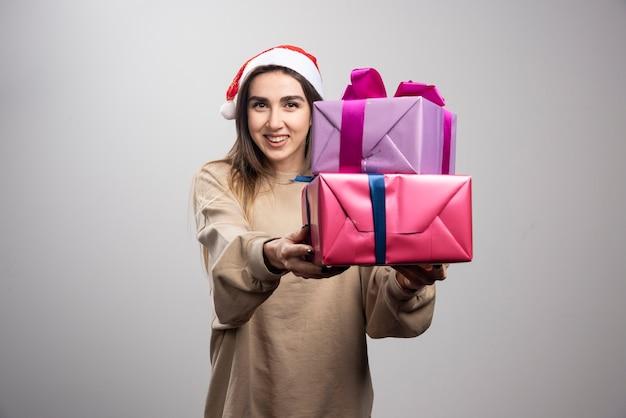 Jovem mulher dando duas caixas de presentes de natal.