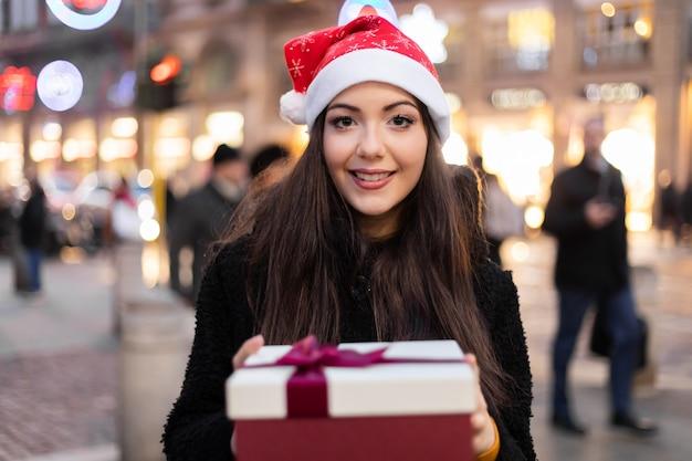 Jovem mulher dando um presente para o natal