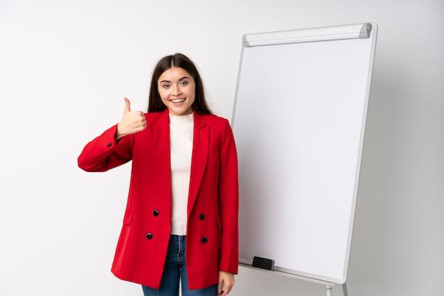 Jovem mulher dando uma apresentação no quadro branco com polegares para cima, porque algo de bom aconteceu