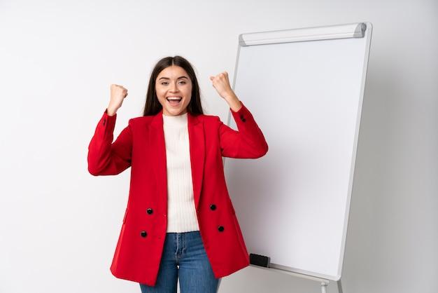 Jovem mulher dando uma apresentação no quadro branco, comemorando uma vitória