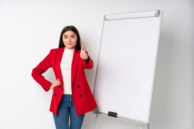 Jovem mulher dando uma apresentação no quadro branco, dando uma apresentação no quadro branco com o polegar para cima