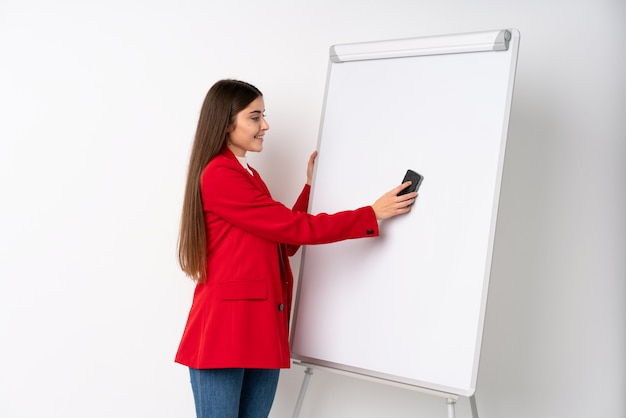Jovem mulher dando uma apresentação no quadro branco, dando uma apresentação no quadro branco