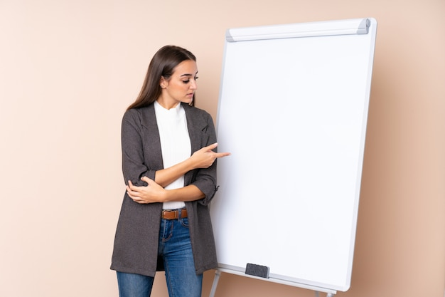 Jovem mulher dando uma apresentação no quadro branco, dando uma apresentação