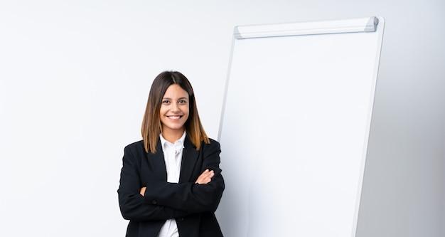 Jovem mulher dando uma apresentação no quadro branco, sorrindo muito