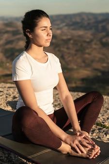 Jovem mulher de alto ângulo meditando