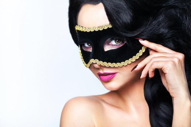 Jovem mulher de atractive com o retrato do estúdio da máscara de veneza.