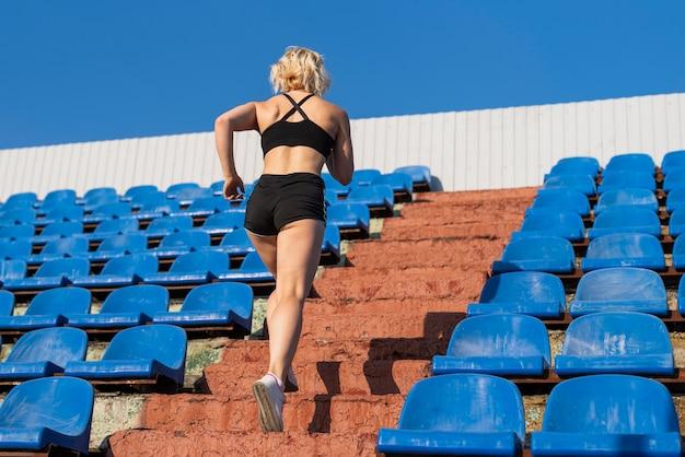 Jovem mulher de baixo ângulo fazendo escadas