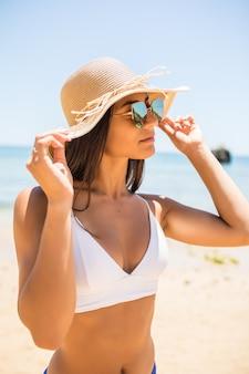 Jovem mulher de biquíni com chapéu de palha branco, aproveitando as férias de verão na praia. retrato de uma linda mulher latina relaxante na praia com óculos de sol.