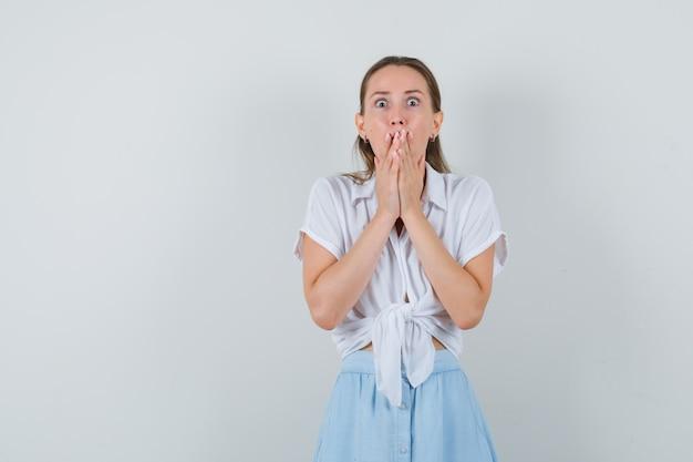 Jovem mulher de blusa e saia de mãos dadas na boca e parecendo assustada