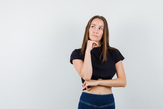 Jovem mulher de blusa preta, calça apoiando o queixo na mão e parecendo pensativa