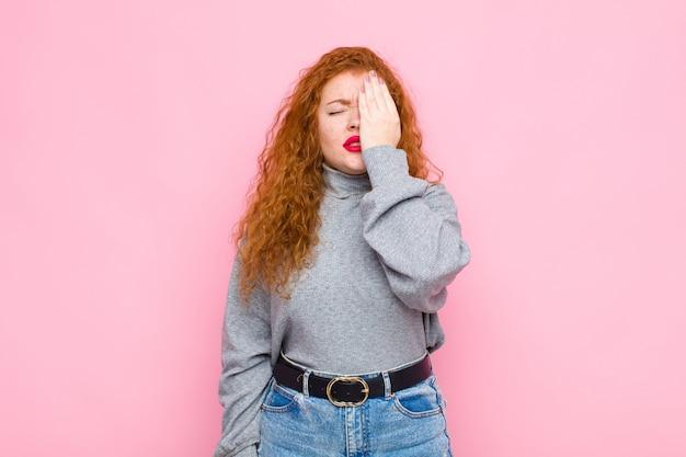 Jovem mulher de cabeça vermelha com sono, entediada e bocejando, com dor de cabeça e uma mão cobrindo metade do rosto na parede rosa