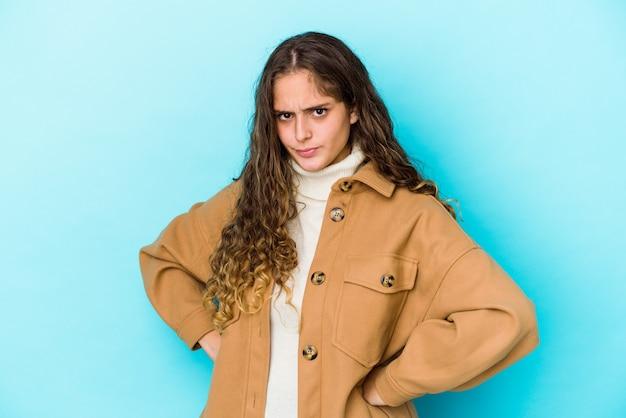 Jovem mulher de cabelo encaracolado caucasiano isolada rosto carrancudo em desgosto, mantém os braços cruzados