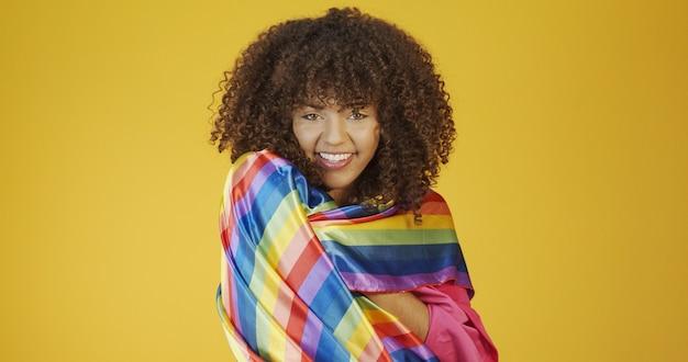 Jovem mulher de cabelo encaracolado cobrindo a bandeira do orgulho lgbt com o punho erguido cobrindo a bandeira lgbt