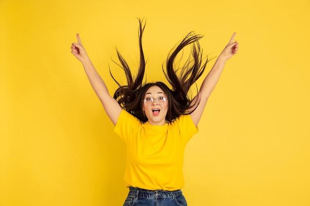 Jovem mulher de cabelo preto em uma camiseta amarela contra uma parede amarela
