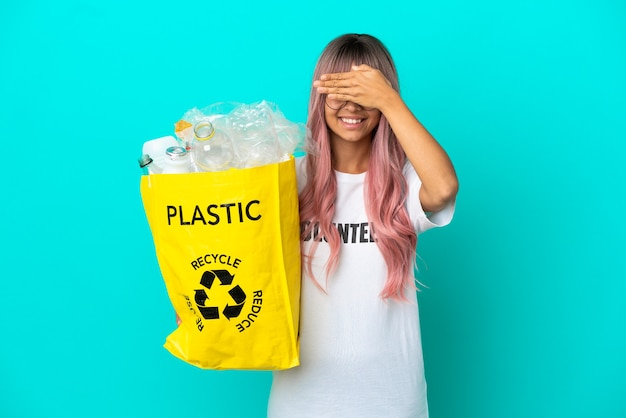 Jovem mulher de cabelo rosa segurando uma sacola cheia de garrafas plásticas para reciclar isoladas em um fundo azul, cobrindo os olhos com as mãos. não quero ver nada