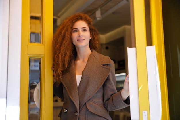 Jovem mulher de cabelo vermelha, saindo de café