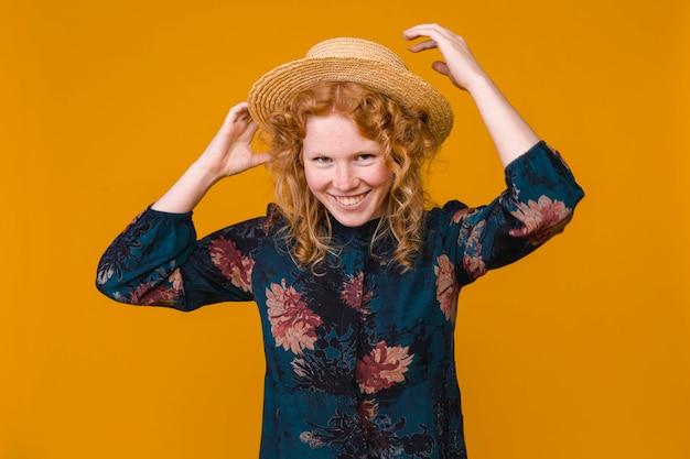 Jovem mulher de cabelo vermelho no chapéu e vestido