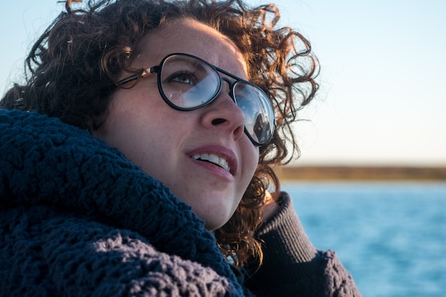 Jovem mulher de cabelos cacheados de óculos em passeio de barco.