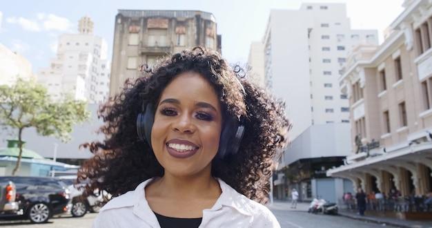 Jovem mulher de cabelos cacheados e fones de ouvido correndo na rua.