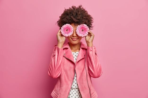 Jovem mulher de cabelos cacheados segura flor gerbera rosa margarida, cobre os olhos, vestida com elegante jaqueta rosa, faz decoração, poses interiores.
