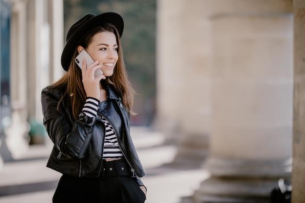 Jovem mulher de cabelos castanhos com jaqueta de couro e chapéu preto no calçadão da cidade conversando por telefone